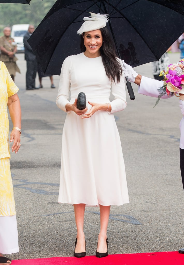 Meghan Markle is saying hello to Fiji in sophisticated and sublime style. The Duchess of Sussex continued her 16-day tour of the South Pacific with husband Prince Harry on Oct. 23, and the duo made a fashionable statement as they walked through the rain, hand in hand. While Meghan defied style rules the day before, she kept things traditional on Tuesday, opting for a white long-sleeved Zimmerman dress and a matching Stephen Jones hat, which she paired with a couple of royally special gifts. Her elegant earrings are actually a gift from Queen Elizabeth herself, and her bracelet comes from Prince Charles. Aw! Such a sweet nod to Harry's family. Check out more snaps of Meghan's full outfit below.      Related:                                                                                                           Exactly What You Can Buy From All of Meghan Markle's Royal Tour Looks