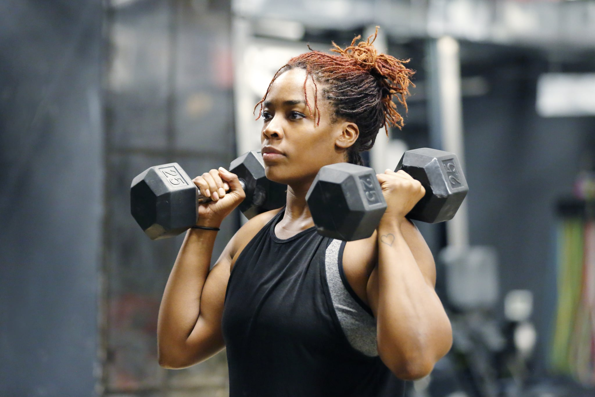 Wasit up image of a fit, young African American woman working out with hand weights in a fitness gym.