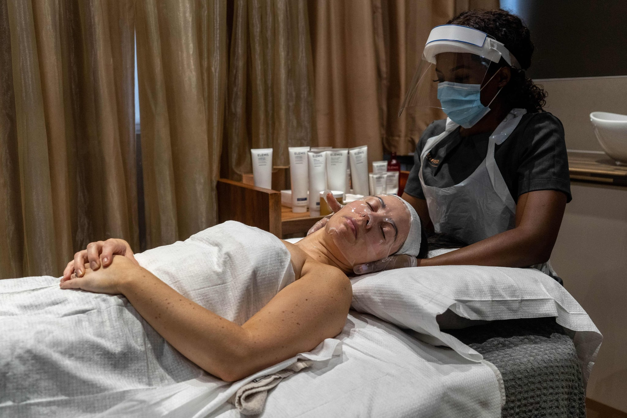 TOPSHOT - Wearing full PPE (personal protective equipment), Theresa Shangazhike, manager of the Spa Experience Wimbledon, gives her client, Lauren Shine a facial treatment in Wimbledon, south London on August 15, 2020, as beauty salons, spas and hairdressers relax the regulations to combat the coronavirus, now offering additional services, including front-of-face treatments. (Photo by Niklas HALLE'N / AFP) (Photo by NIKLAS HALLE'N/AFP via Getty Images)
