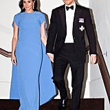 "Meghan's ""borrowed"" chandelier earrings turned up the glamour when teamed with this Safiyaa cape gown at a state dinner in Fiji."