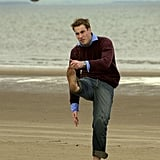 The royal played with a rugby ball during a trip to the beach in May 2003.
