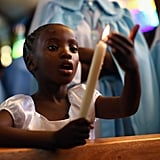 A young girl held up a candle during South Africa's national day of prayer for Nelson Mandela.