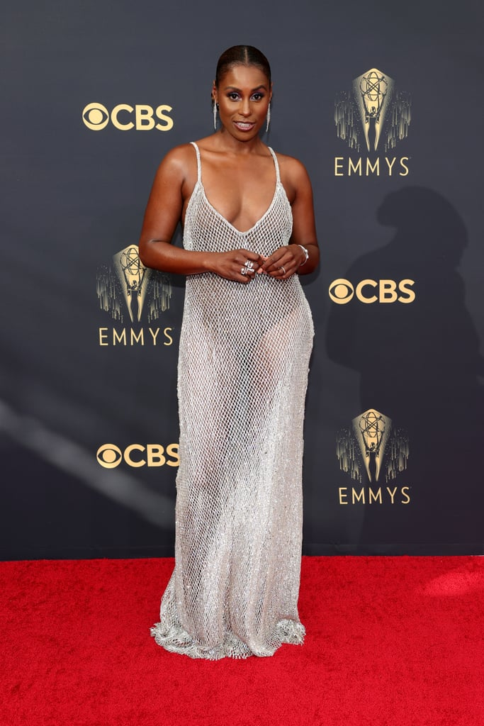 The votes have been counted and the results are in for the 2021 Emmys, and our main takeaway? Issa Rae looked damn good in a custom Aliétte dress on the red carpet. Draped from the shoulders down in a mesh curtain of crystals, the Insecure star looked anything but, wearing nothing but a pair of black briefs beneath the sheer gown. Shimmering from head to toe, Issa let the look, designed and styled by Jason Rembert, speak for itself, pairing it with a Marli New York geometric double-finger ring and a diamond grill, a set of silver Fernando Jorge feather earrings, and smoky purple eyeshadow.  We don't know how hot it is inside the Event Deck, but Issa is sure to raise the temperature as soon as she steps inside. Read on to see her glittering dress from all angles ahead, and see more extravagant outfits from this year's Emmy Awards here.       Related:                                                                                                           ICYMI, Binge-Watch the Emmys Red Carpet Right Here