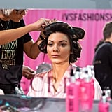 Kendall Jenner looks at her flawless skin as she gets her hair tucked into rollers.