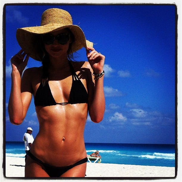 Miranda Kerr shaded her face from the sun with a straw hat. Source: Instagram user mirandakerrverified