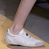 A mesh white low-top emblazoned with the designer's initials.
