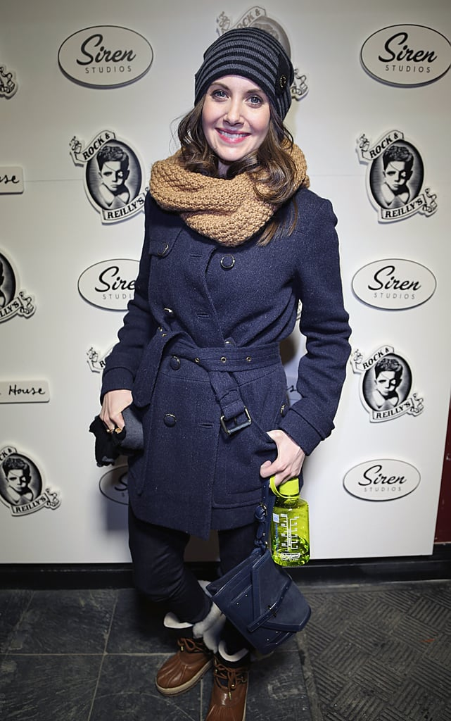 Alison Brie beat the Winter blues with a belted coat, striped beanie, and mixed-texture Tory Burch clutch.