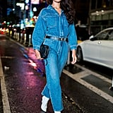 Shanina Shaik styling a denim jumpsuit with white boots.