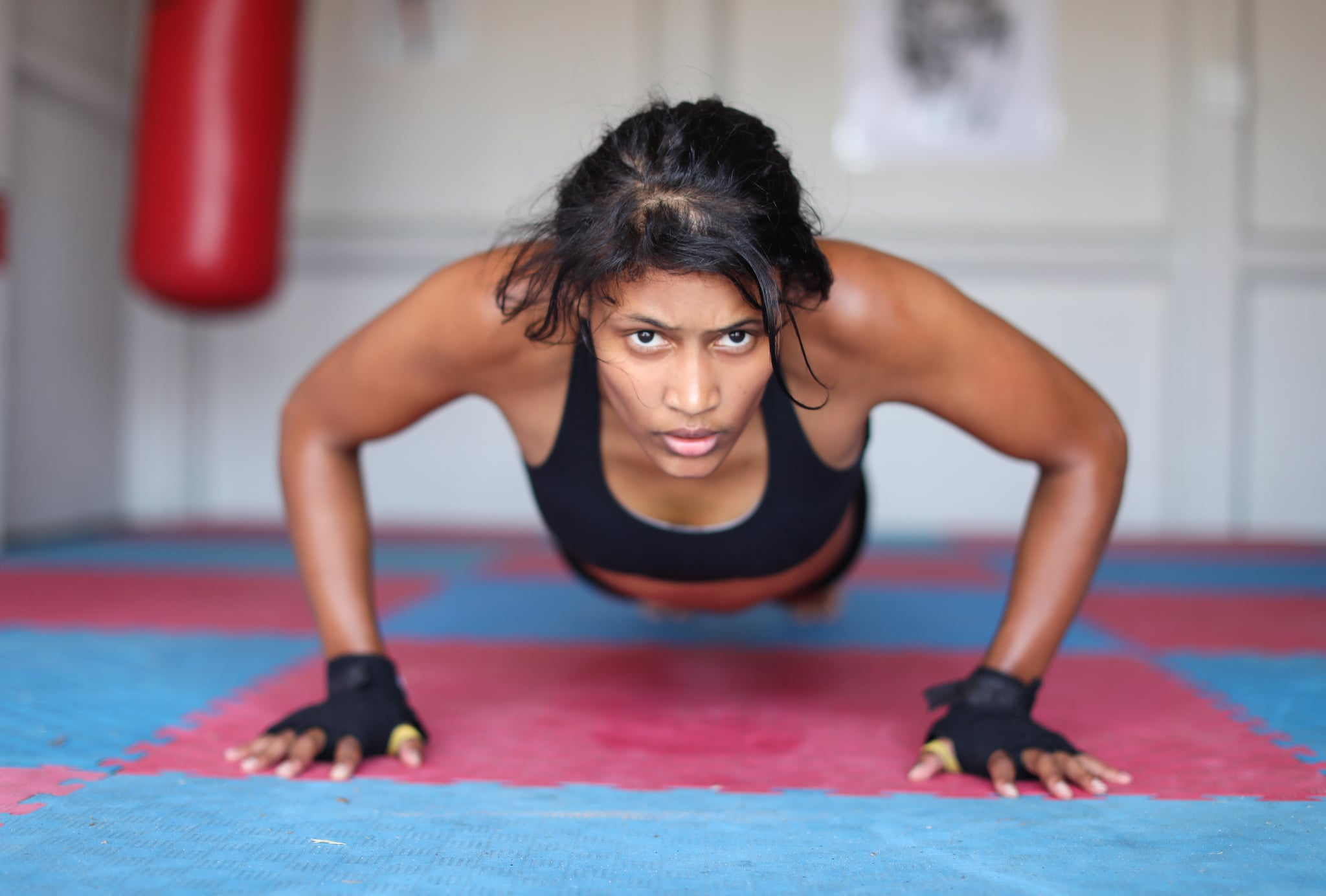 a Young woman training alone in a Thai Boxing Dojo.