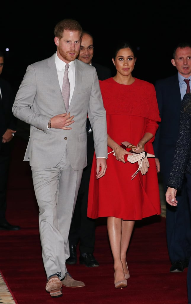 """Prince Harry and Meghan Markle made it to Morocco, and once again they look absolutely stunning. As the couple made their first appearance of the trip, the Duchess of Sussex wowed fans in a detailed Valentino cape dress. The gown could be a nod to the designer's Spring 2013 Couture collection.  Meghan paired the radiant red gown with neutral pumps and a blush Valentino handbag with matching gloves. I can only imagine what other fabulous fashion picks Meghan has in store for the rest of trip! Ahead, see more snaps of Meghan's outfit and shop similar dresses for yourself.       Related:                                                                                                           It Doesn't Get Any Sweeter Than Meghan Markle's """"Mummy"""" Necklace"""