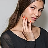 Orange nails with a simple face at Suno.