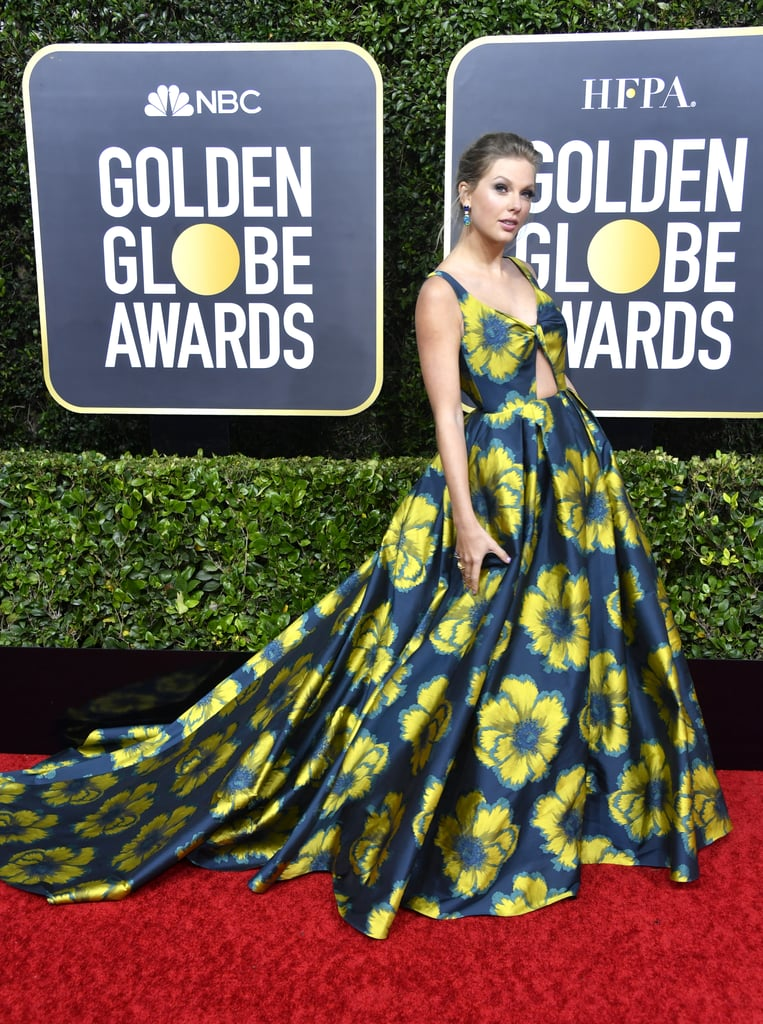 """Taylor Swift brought the flower power to Sunday night's Golden Globes in Beverly Hills. The 30-year-old singer is nominated for the original song """"Beautiful Ghost"""" from the movie-musical Cats, and she certainly dressed like a winner in a dramatic custom Etro Couture ball gown with printed flowers. She quickly walked the red carpet solo, but met her boyfriend Joe Alwyn inside. I would've loved to hear what he had to say about her glam navy dress — and that keyhole cut-out! Ladies and gentlemen, will you please stand? This look deserves a round of applause.  Check out more glimpses of her gown from all angles, ahead."""