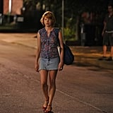 Margot walking at night in a sleeveless floral blouse, a denim cutoff skirt, and red ankle-strap sandals. To achieve her look, shop this Equipment floral blouse ($188), this denim skirt ($105), and these Oscar de la Renta red ankle-strap wedges ($865).