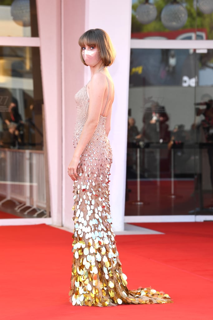 "Maya Hawke stepped out for the 77th Venice Film Festival on Sept. 5 and, wow, she stunned. The 22-year-old actress and singer showed up to the affair modeling a gorgeous Versace mermaid gown with a matching blush pink face mask and a short bob haircut, which her mom, Uma Thurman, snipped herself. The Stranger Things star's appearance followed her Sept. 4 red carpet arrival where she sported another gorgeous look, wearing a black turtleneck tank top with a floral pleated skirt.  Maya — who recently released her debut album, Blush — attended the event for the premiere of the Gia Coppola-directed drama, Mainstream. The film is described as cautionary tale in which ""three people struggle to preserve their identities as they form an eccentric love triangle within the fast-moving internet age."" Maya stars as a character named Frankie, alongside Andrew Garfield, Nat Wolff, and Euphoria's Alexa Demie. See more snaps from Maya's photocalls at the festival ahead!"