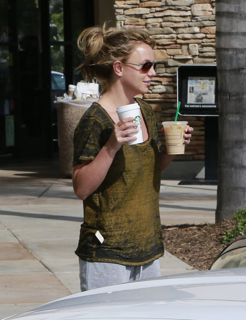 Britney Spears held two drinks as she and David Lucado made their way to the car.