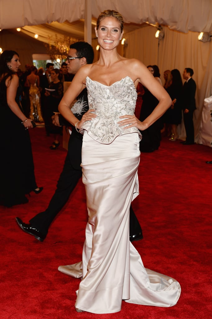 Heidi Klum showed off her décolletage in a metallic bustier embroidered gown by Marchesa, Jimmy Choo heels, and Harry Winston jewels.