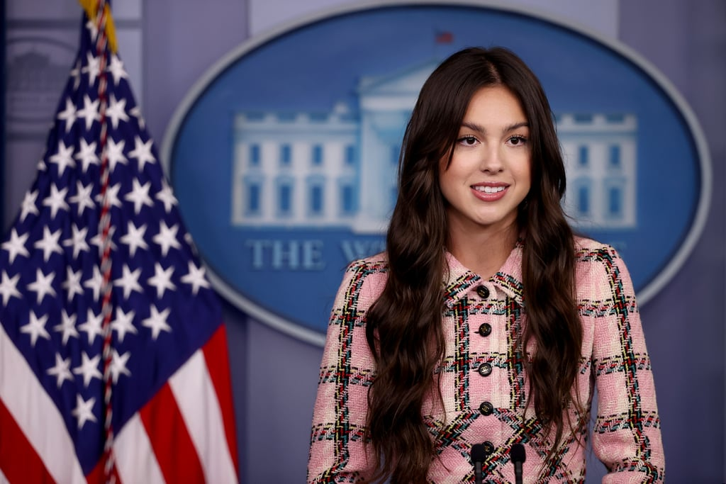 """Olivia Rodrigo is using her platform for good. On Wednesday, the """"Drivers Licence"""" singer made a trip to the White House to encourage people to get the COVID-19 vaccine. Seemingly channelling her inner Elle Woods, Olivia wore a pink tartan dress suit and white platform high heels as she made her way inside for the important visit. Reporters also shared a few snapshots of Olivia getting the grand tour of the White House as she visited the West Wing.  During her visit, Olivia is set to meet with President Joe Biden and Dr. Anthony Fauci and will record a handful of videos encouraging her followers to get vaccinated as well as answer a few questions. Olivia and President Biden previously teased her visit on Instagram on Tuesday when the president shared a throwback photo of him, writing, """"I know this young person would've gotten vaccinated, but we've got to get other young people protected as well. Who's willing to help?"""" Olivia eventually chimed in, writing, """"i'm in! see you tomorrow at the white house!"""" See more pictures from her White House visit ahead.       Related:                                                                                                           Which Song From Olivia Rodrigo's Sour Album Are You, Based on Your Zodiac Sign?"""
