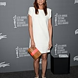 Kristen Wiig was playful in a white Saint Laurent t-shirt dress, gray suede pumps, and a two-toned envelope clutch at the Costume Designers Guild Awards in Beverly Hills.
