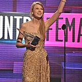 Taylor Swift waved to the crowd while accepting her award for favorite country female artist.