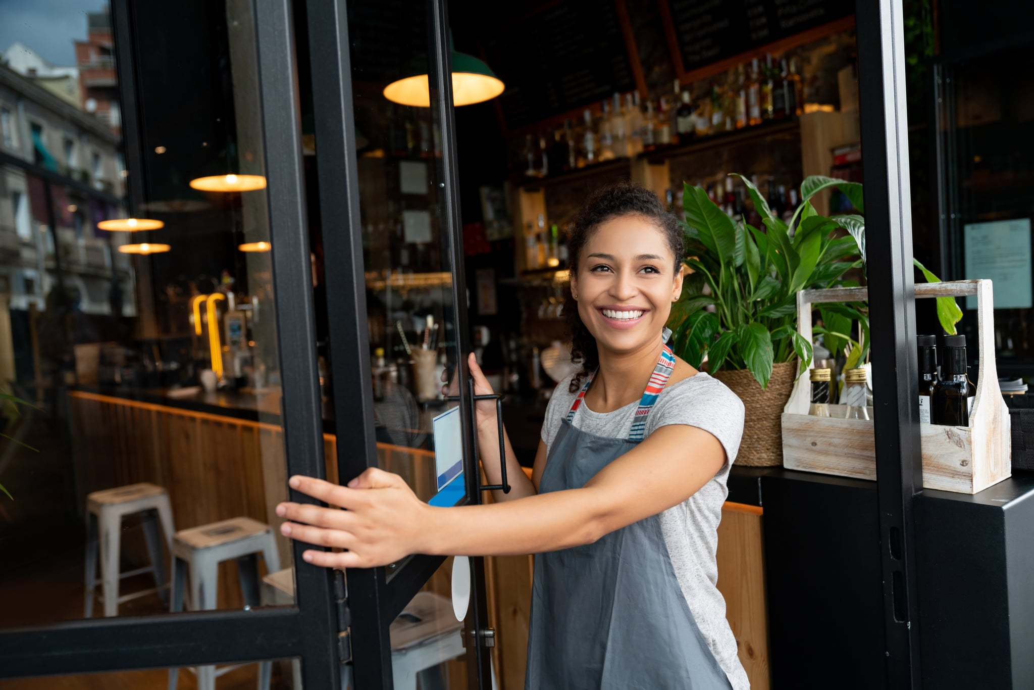 Portrait of a happy business owner opening on the door at a cafe and smiling – small business concepts