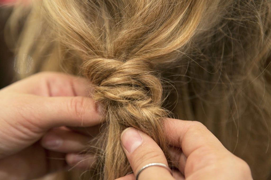 Wrap the braid around the base of the ponytail, and tuck the ends of the braid into the elastic for a seamless finish.