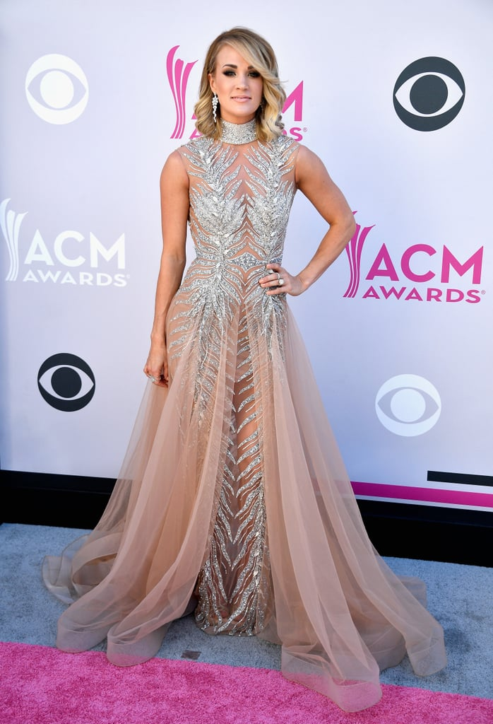 Carrie Underwood hit up the ACM Awards in Las Vegas on Sunday looking like some sort of angelic dream. The singer, who is set to perform tonight, practically floated down the red carpet in a sparkly blush and silver gown. Carrie is up for two awards, including entertainer of the year, and if her performance is anything like last year's, we're in for a real treat.