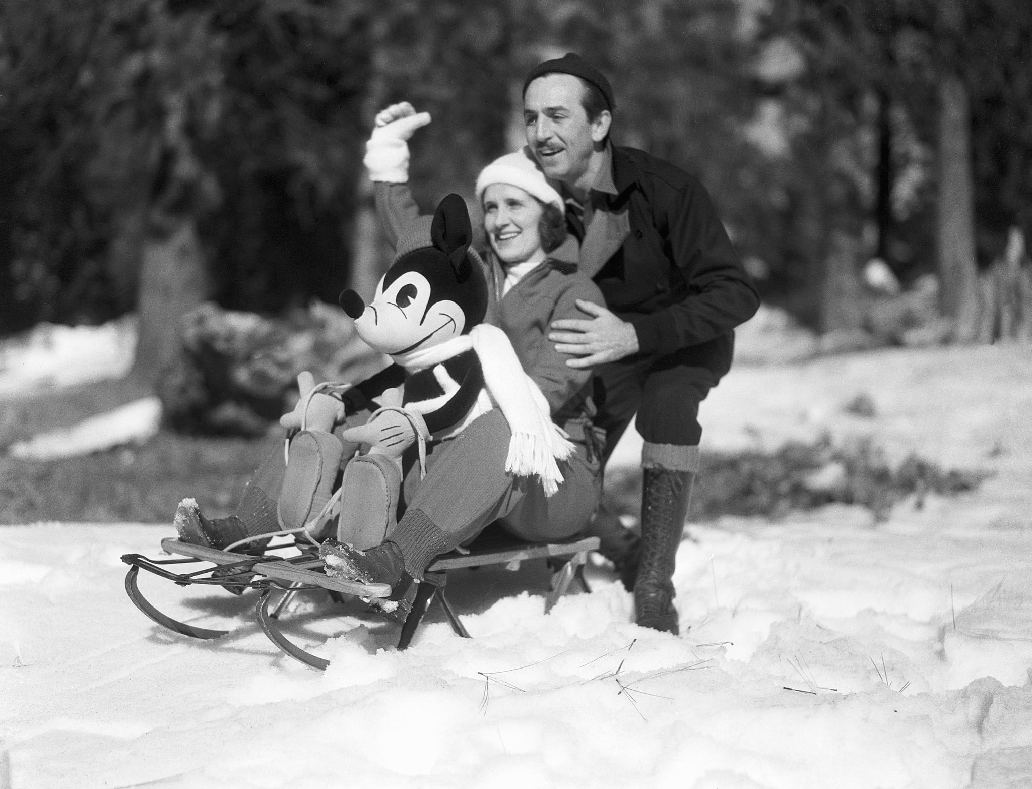 Mr. and Mrs. Walt Disney rest on a sled with a stuffed Mickey Mouse as they greet children to a snow party at the Lake Arrowhead resort area.