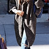 Kate Beckinsale bundled up in a long herringbone coat, American Colors flannel, black suede booties, and signature shades during a chilly NYC trip in October 2008.