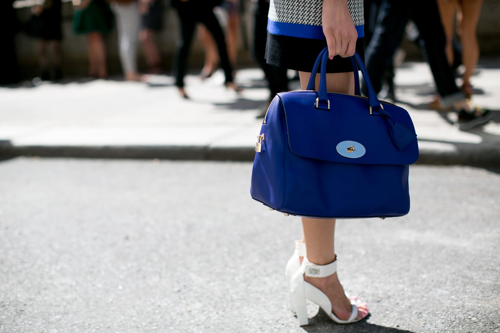 Bold blue on her bag, sleek white on her heels.