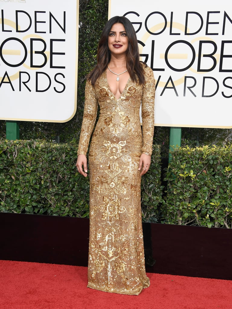 Priyanka Chopra in a gilded Ralph Lauren gown with a plunging neckline, Brian Atwood shoes, and Lorraine Schwartz jewels in 2017.