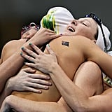Australia's Alicia Coutts, Cate Campbell, Brittany Elmslie, and Melanie Schlanger had a group hug after winning their freestyle relay final swimming event.