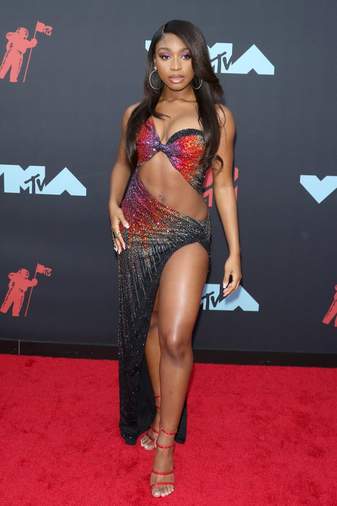 "Never underestimate the power of Normani and her kickass wardrobe. The 23-year-old singer showed up to the MTV VMAs on Monday night, and absolutely shut down the red carpet in a skin-baring Swarovski crystal-covered Nicolas Jebran dress with a high-slit. If that wasn't  enough, she tied the whole look together with silver hoops and studded matte red sandals. Phew, what. an. outfit.  Like her viral ""Motivation"" music video, it feels like Normani packs in a whole bunch of late '90s/early '00s nostalgia into this ensemble (the exposed midriff, sparkling crystals) while still making it completely her own. If this is what she chose to rock on the red carpet, we can't wait to see what she wears during her performance later in the show."