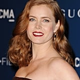 Amy Adams mixed multiple shades of red, from her dark Merlot lipstick to her curly auburn strands.