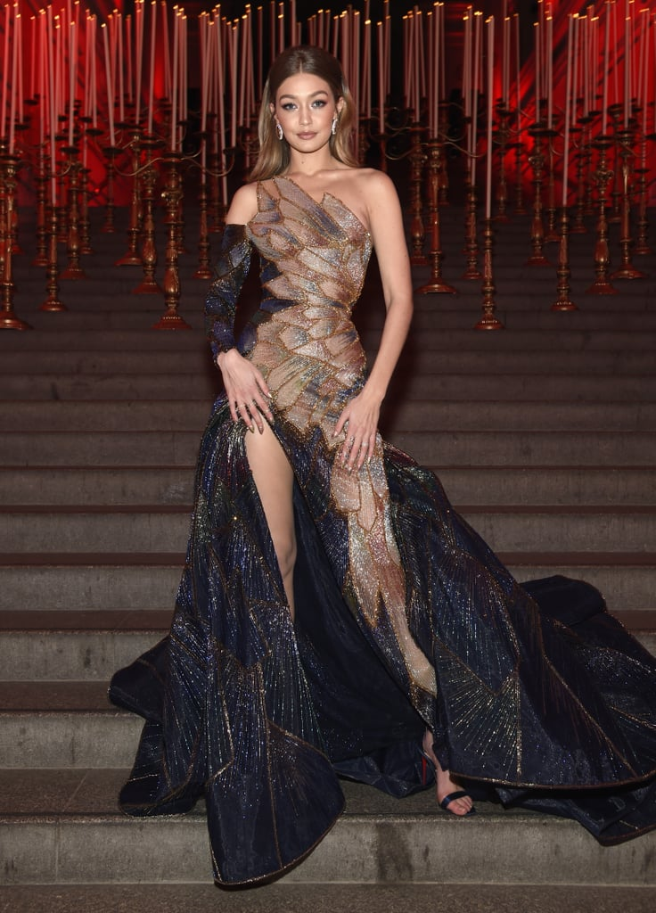 "Keeping up with the ""Heavenly Bodies: Fashion and the Catholic Imagination"" theme, Gigi Hadid's custom Versace gown for the 2018 Met Gala was inspired by the stained glass windows of a church. But it's not the glass-inspired details you'll see right through . . . it's the sky-high slit that shows off her entire leg! If that's not enough, then wait until you see it from behind, where cutout pieces truly hammer home the inspiration behind Gigi's gown. The 23-year-old model's shimmering Versace gown is a true work of art, complete with shimmering segments of fabric stitched together to create a flowing, single-sleeved masterpiece reminiscent of an ancient cathedral. Gigi accessorized the dress with simple drop earrings and a sleek hairstyle.  Keep scrolling to see every angle of the getup, then follow along with the rest of our Met Gala coverage to see every jaw-dropping outfit of the evening."