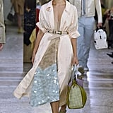 Since Melania tends to belt her looks, we can imagine her employing the style trick with this sophisticated trench. Would she be designer ready without a flashy material peeking out from underneath?