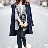 خذي النصيحة من نجمة موضة الشارع هذه واشتري معطف كحلي اللون. فهذا اللون يتماشى مع كل ثيابك كاللون الأسود تماماً.