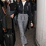 Kaia wearing a pair of high-waisted check Self-Portrait trousers with a black moto jacket.