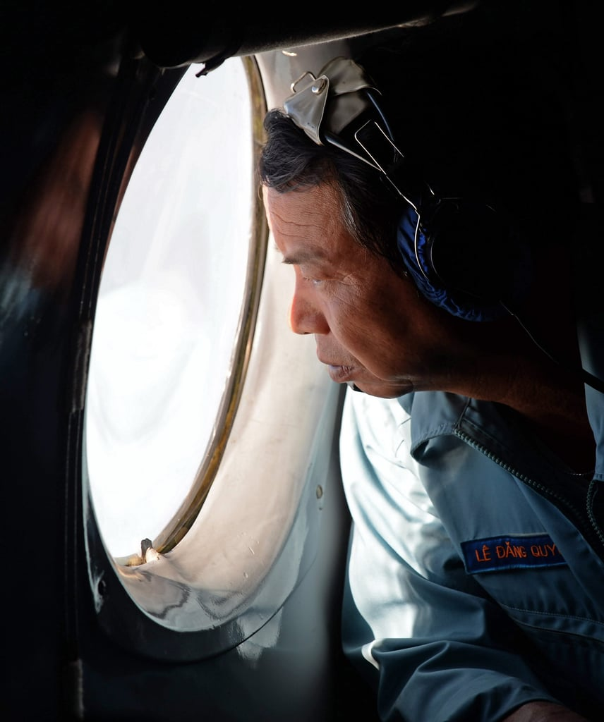 As the investigation continued, a Vietnam Air Force officer looked out the window of a search aircraft on Sunday.
