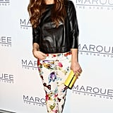 Minka Kelly accessorized her look with a yellow clutch to play off the hues on her floral-print pants.