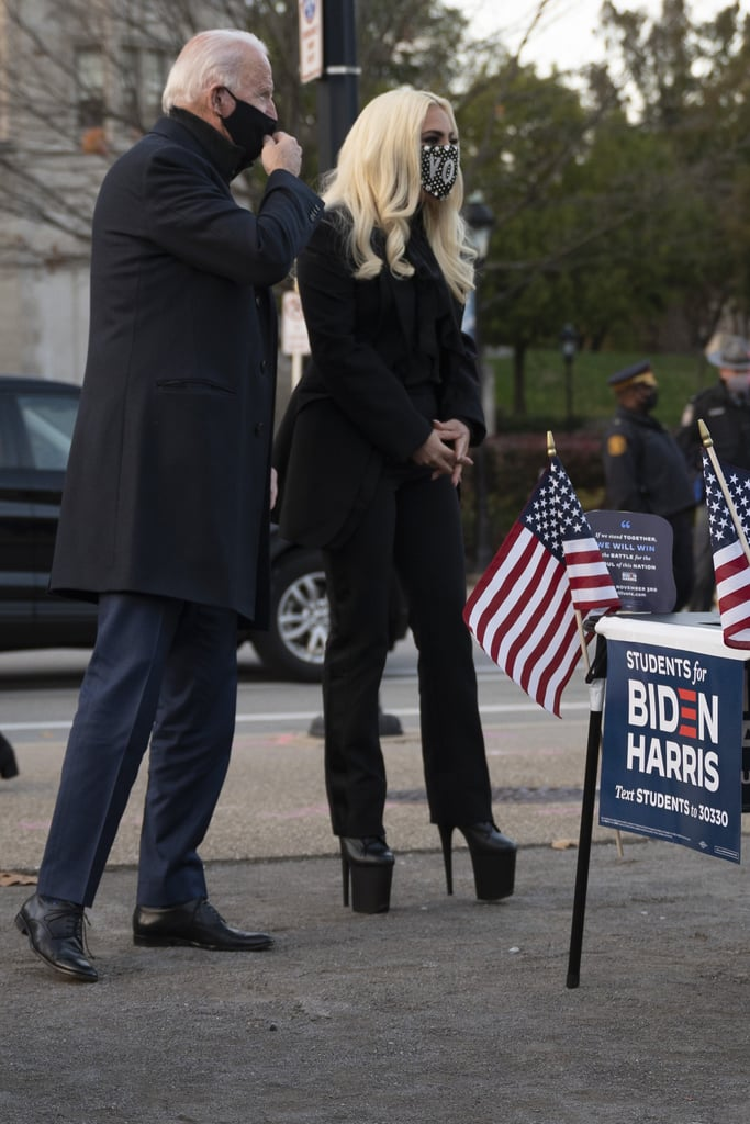 "Lady Gaga absolutely meant business when she showed up for the Biden-Harris campaign's last rally in a power suit and platform boots on Nov. 2. The ""Rain on Me"" singer made an appearance in Pittsburgh the evening before the 2020 presidential election, to make a final plea to voters to cast their ballots for the former vice president.  In a sea of dress shoes, Gaga stood out from the rest of the crowd — literally — in sky high shoes from Pleaser. Her sleek black suit came from designer Alexander McQueen, as did her dangling locket earrings. She tied the whole look together with a statement face mask (she's the queen of them, at this point) with a rhinestone-encrusted ""Vote"" message printed across the front. Lest you forget, there's still time to vote in-person tomorrow. Listen to Gaga, and get ready!       Related:                                                                                                           Lady Gaga Has Voting Outfits For Days, to No Surprise, and Now She Wants You to Share Yours"