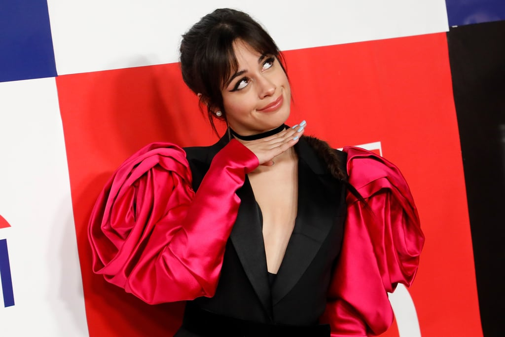 """Somewhere in Underland, the Queen of Hearts just lost her crown, because Camila Cabello looked like absolute royalty in this mini suit jacket dress with poofy pink rose sleeves on Thursday — the flowers are bigger than her face! The """"Señorita"""" singer rocked the stunning suit dress on the red carpet of Time's 100 Next 2019 event in New York City, and something tells me her look would leave Alice in Wonderland shaking.  Camila completed the look with pearl earrings, fishnet tights, and a pair of black thigh-high, velvet boots. Considering her steamy relationship with Shawn Mendes and her soon to be released album, Romance, it's no surprise that Camila would wear such a romantic look on the red carpet. Keep scrolling to take a closer look at her entire outfit ahead."""