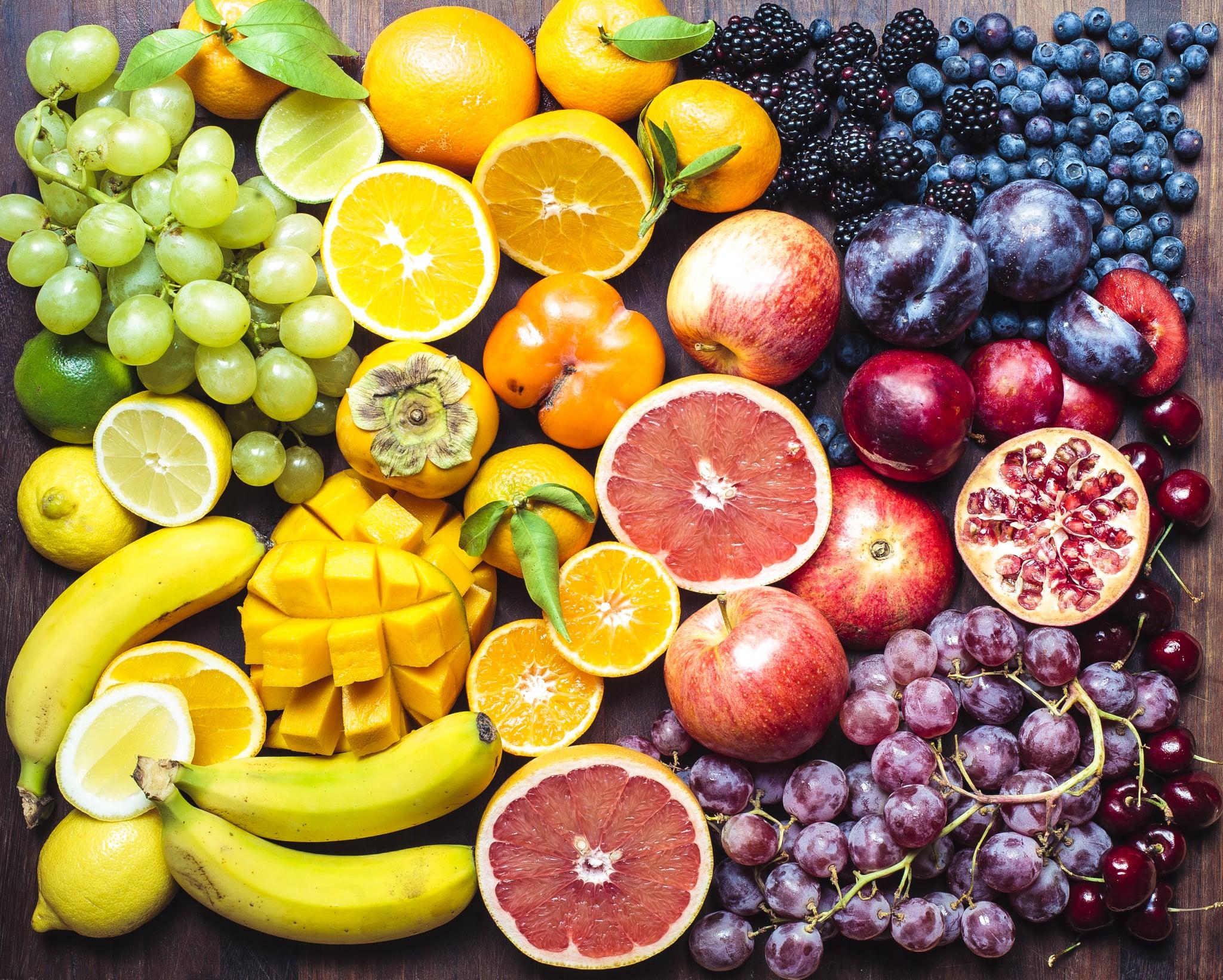 A colourful spectrum of fruit: oranges, lemons, limes, mandarins, grapes, plums, grapefruit, pomegranate, persimmons, bananas, cherries, apples, mangoes, blackberries and blueberries.