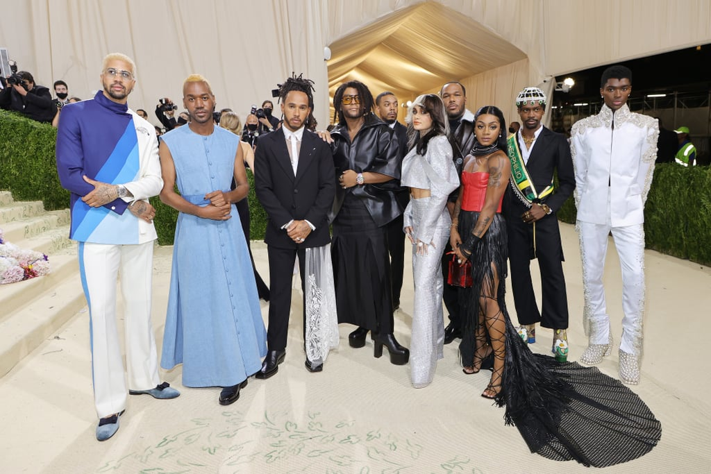 """After being canceled due to COVID-19 last year, the Met Gala, fashion's biggest event of the year, was back with a bang last night in New York City. Cohosted this year by singer Billie Eilish, poet Amanda Gorman, actor Timothée Chalamet, and tennis player Naomi Osaka, the event undoubtedly makes top billing in the celebrity calendar, drawing the hottest names in the business to showcase their ensembles for the evening and fundraise for the Metropolitan Museum of Art. For the 2021 event, the selected theme was """"In America: A Lexicon of Fashion,"""" and Vogue reported that Met Gala regular and fashion icon Lewis Hamilton chose to use his influence to showcase Black designers at the event. A frequent Met Gala attendee, the seven-time Formula One champion is known for wearing the work of high-profile designers. This year, however, Hamilton invited three emerging Black designers to his table, which can cost up to $30,000. Historically, tables are often bought up by the biggest creatives in the industry, who use the seats for celebrities they have dressed for the evening, which hasn't been great for making the Met Gala an inclusive and diverse event in the past.  Having started The Hamilton Commission to improve Black representation within UK motorsports, Hamilton is said to have realized that the fashion industry equally requires brands and designers to be given more opportunities to make names for themselves. Having been excited by the designs of Theophilio, Kenneth Nicholson, and Jason Rembert over the past 18 months, Hamilton chose to share his table with them, to both showcase the theme of the evening and begin efforts to diversify the fashion world. """"The Met is the biggest fashion event of the year, and for this theme, I wanted to create something that was meaningful and would spark a conversation,"""" Hamilton told Vogue. """"So that when people see us all together, it will put these Black designers at the top of people's minds."""" In addition to his organization to improve r"""