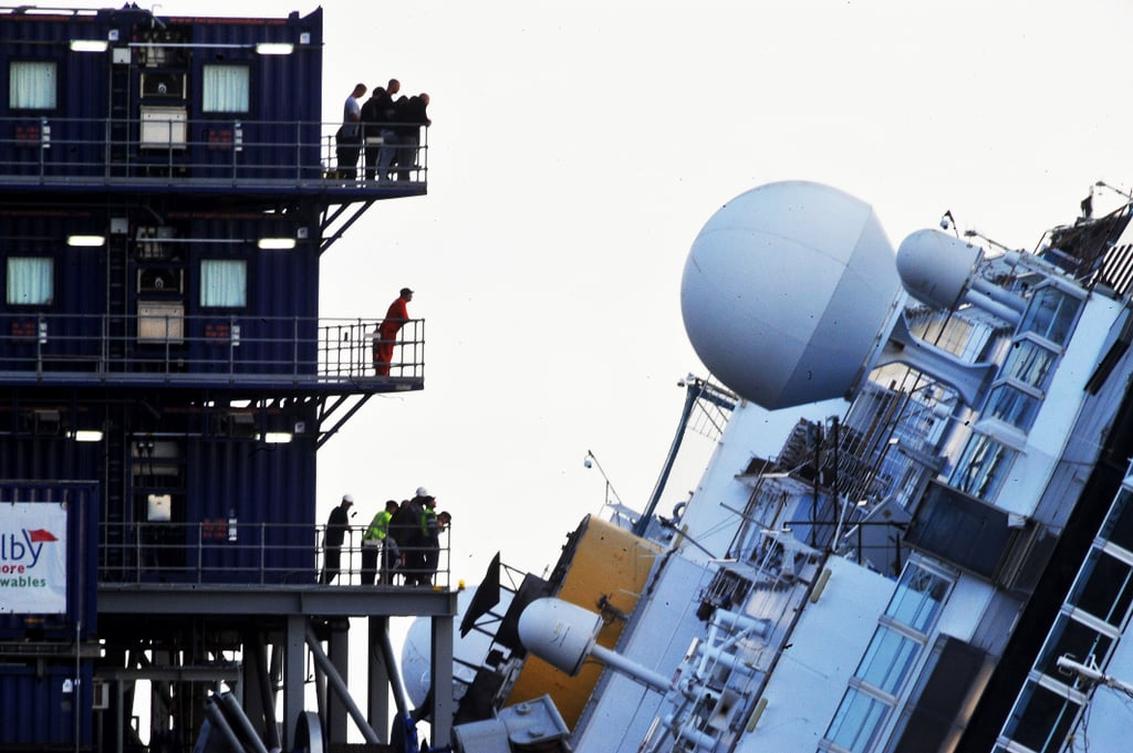 Standing on platforms, the workers looked on as they prepared to right Costa Concordia.