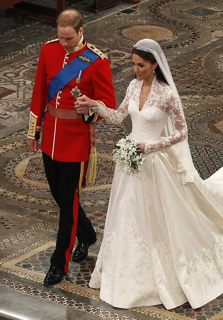 ">> More details about Kate Middleton's Sarah Burton-designed Alexander McQueen dress — apparently its seamstresses had to wash their hands every 30 minutes to keep the lace pristine, and the train is 107 inches long, or just under 9 feet. From the release: ""The lace appliqué for the bodice and skirt was hand-made by the Royal School of Needlework, based at Hampton Court Palace.  The lace design was hand-engineered (appliquéd) using the Carrickmacross lace-making technique, which originated in Ireland in the 1820s.  Individual flowers have been hand-cut from lace and hand-engineered onto ivory silk tulle to create a unique and organic design, which incorporates the rose, thistle, daffodil and shamrock."" ""Hand-cut English lace and French Chantilly lace has been used throughout the bodice and skirt, and has been used for the underskirt trim.  With laces coming from different sources, much care was taken to ensure that each flower was the same colour.  The whole process was overseen and put together by hand by Ms Burton and her team."" ""The dress is made with ivory and white satin gazar.  The skirt echoes an opening flower, with white satin gazar arches and pleats.  The train measures two metres 70 centimetres.  The ivory satin bodice, which is narrowed at the waist and padded at the hips, draws on the Victorian tradition of corsetry and is a hallmark of Alexander McQueen's designs.  The back is finished with 58 gazar and organza covered buttons fastened by Rouleau loops.  The underskirt is made of silk tulle trimmed with Cluny lace."" Middleton also wore handmade McQueen shoes, a Cartier tiara, and Robinson Pelman earrings. In accordance with tradition, her ""something old"" was the influence of the Carrickmacross lace-making technique, the earrings were her ""something new"" and a blue ribbon sewn into her dress was her ""something blue."""