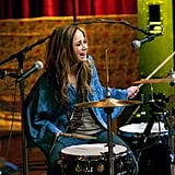 Remember when oversize capes were a thing? Roxy is a boho pro in hers while playing the drums.