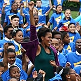 Michelle Obama and adorable kids do jumping jacks.