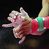 A gymnast chalks his hands in preparation for the parallel bars.