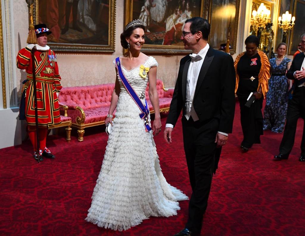 "Kate Middleton was an absolute vision in white when she stepped out for the State Banquet with Prince William at Buckingham Palace on Monday. The Duchess of Cambridge stunned in an Alexander McQueen gown and the Lover's Knot tiara, while William looked debonair in a black tux. The black-tie affair was hosted by Queen Elizabeth II in honour of US President Donald Trump's UK visit, and also brought out Prince Charles, Camilla, Duchess of Cornwall, US Secretary of the Treasury Steven Mnuchin, Prime Minister Theresa May, and Donald's family, including his wife Melania, daughters Ivanka and Tiffany, and sons Donald Jr. and Eric. During the event, the queen delivered a speech, highlighting the importance of the UK's relationship with the US. ""Tonight we celebrate an alliance that has helped to ensure the safety and prosperity of both our peoples for decades, and which I believe will endure for many years to come,"" Elizabeth said. She then raised a toast to ""the continued friendship between our two nations, and to the health, prosperity and happiness of the people of the United States."" Neither Prince Harry nor Meghan Markle were present at the banquet, as they recently welcomed their son Archie and the Duchess of Sussex is currently on maternity leave. However, Harry did have a meeting with the Trump family earlier in the day. See more of William and Kate's glamorous night out ahead!       Related:                                                                                                           23 Times Will and Kate Showed PDA — and Why They Don't Do It That Often"