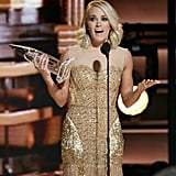 As she took the stage to accept her award, Carrie wore a beaded, gold minidress.